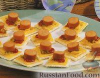 Фото к рецепту: Закуска на крекерах, с сыром и сосисками