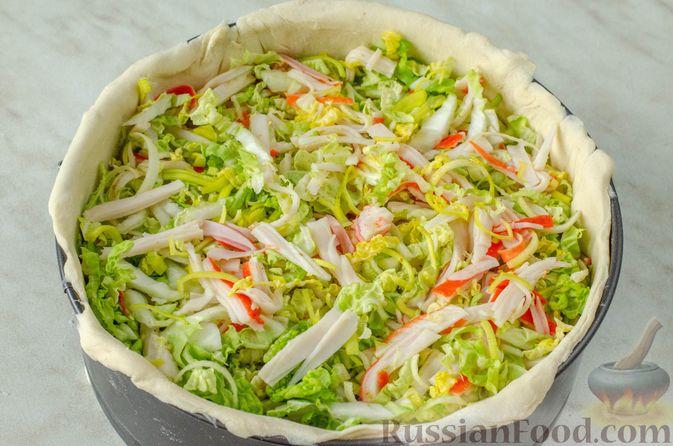 Фото приготовления рецепта: Киш из слоёного теста с крабовыми палочками, пекинской капустой и луком-пореем - шаг №12