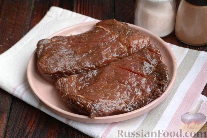 Фото приготовления рецепта: Бифштекс в маринаде с соевым соусом, чесноком и мёдом - шаг №7