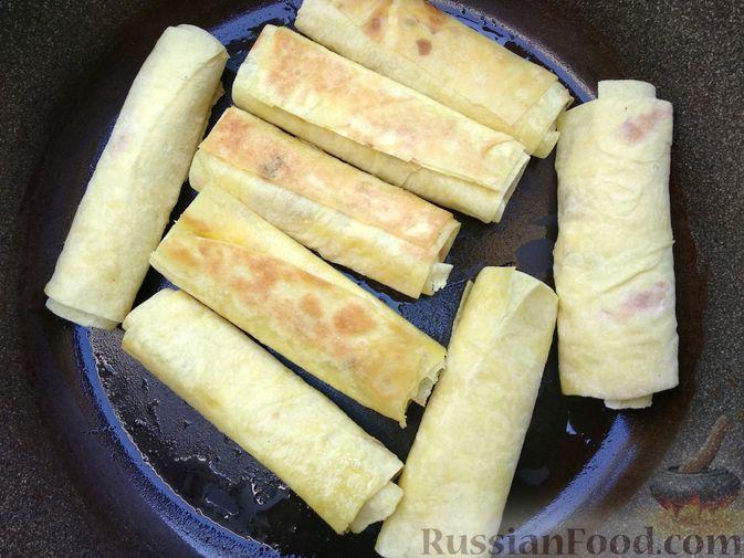 Фото приготовления рецепта: Рулетики из лаваша с творогом, клюквой и шоколадом (на сковороде) - шаг №9