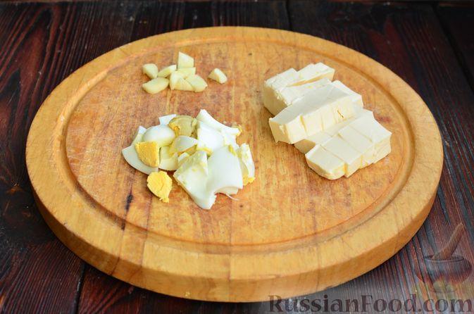 """Фото приготовления рецепта: Закуска """"Ёлочки"""" на крекерах, с плавленым сыром, яйцом и зеленью - шаг №2"""