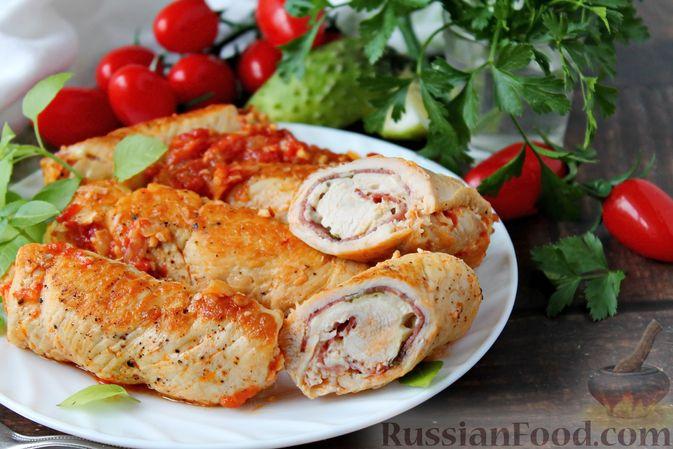 Фото к рецепту: Куриные рулетики с ветчиной и моцареллой, тушенные в томатном соусе