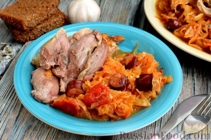 Фото к рецепту: Свиная рулька, запечённая с кислой и свежей капустой и копчёными колбасками