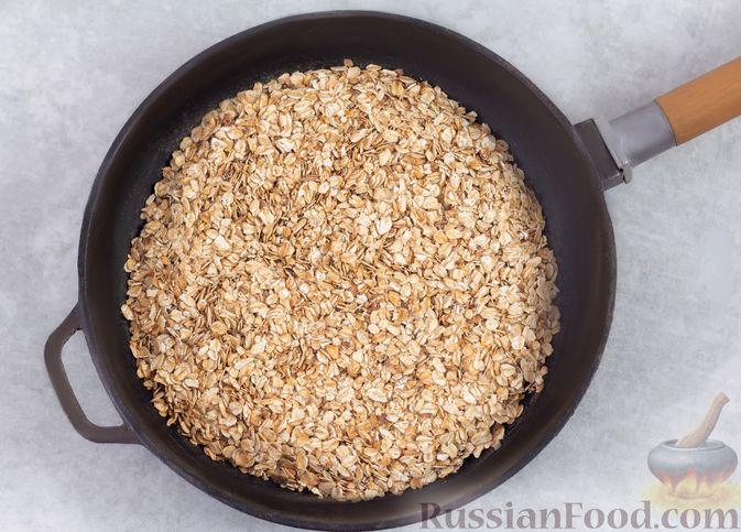 Фото приготовления рецепта: Гранола с орехами, изюмом и мёдом (на сковороде) - шаг №4