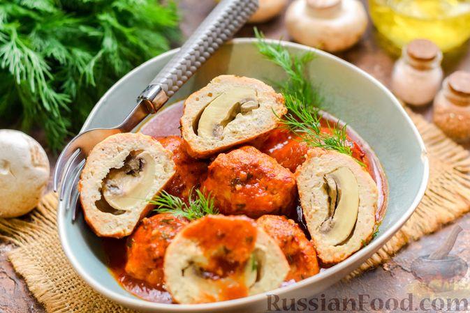 Фото к рецепту: Мясные тефтели с начинкой из целых шампиньонов, запечённые в томатном соусе