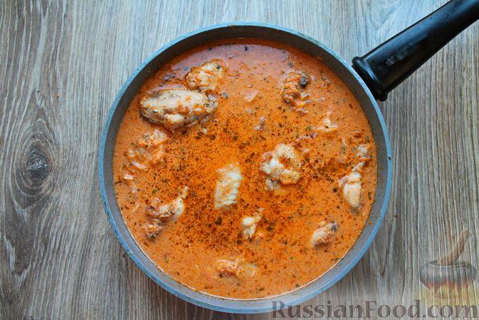 Фото приготовления рецепта: Куриные крылышки, тушенные в сметанно-томатном соусе - шаг №11